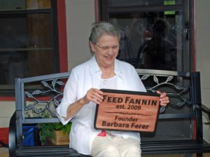 Feed Fannin founder Barbara Ferer smiling, holding a plaque with her name on it.
