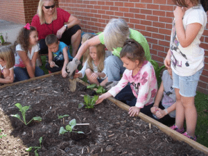 Feed Fannin volunteer planting a raised bed with elementary school students.